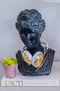 Home office styling with vintage bust and gold headphones