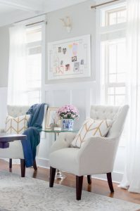 Light Colored tufted armchair with navy throw