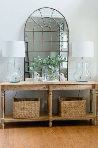 Welcome your guest in style with a pretty entry. Everett foyer table styling with pretty lamps, arch mirror and baskets.
