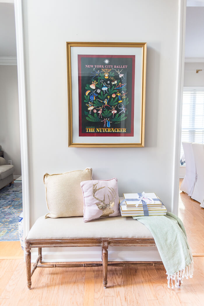 Christmas entryway with Nutcracker print and french bench. #thehomeicreate #poinsettias #entrywaydecor #christmasdecor