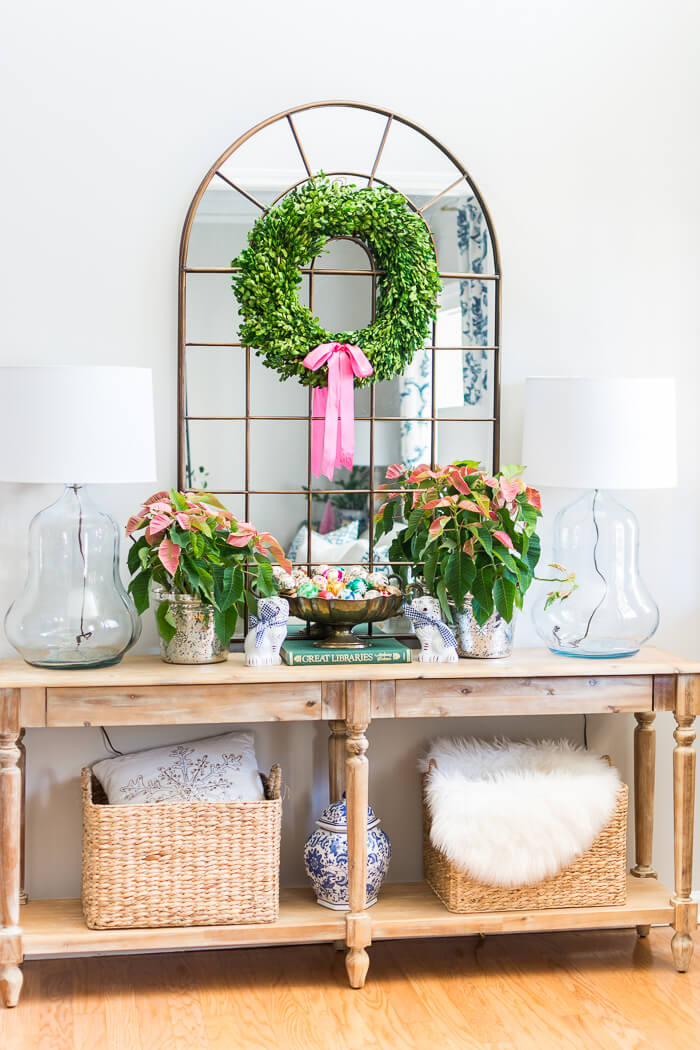 Colorful Christmas entryway with pink poinsettias and boxwood wreath. #thehomeicreate #poinsettias #entrywaydecor #christmasdecor