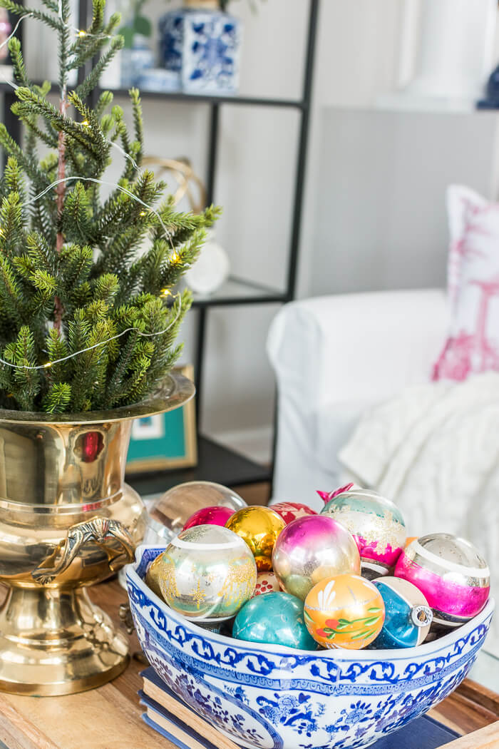 Colorful Christmas living room with vintage shiny brite ornaments in a blue and white bowl . #thehomeicreate #blueandwhite #livingroomdecor #christmasdecor