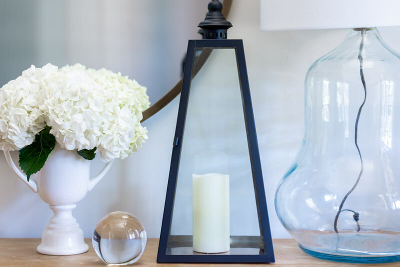 Entryway table with lantern, flowers and lamp